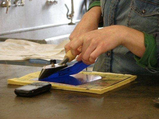 Ironing the film to the plate with a tacking iron.